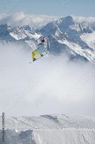 Snowboarder jumping high in the mountains