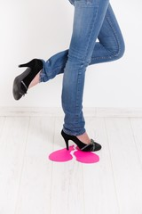 Sexy legs trampling on pink paper heart