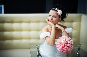 Beautiful bride with bouquet of flowers on modern interior