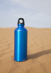 Blue sport water bottle in desert