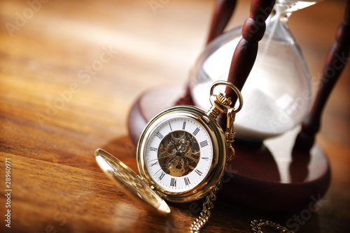 Gold pocket watch and hourglass