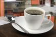 Taza de café blanca con cocina de fondo
