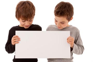 Zwei Jungen - Zwillinge halten ein weißes Schild