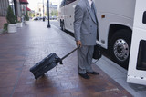 Businessman with suitcase getting into a bus