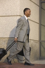 Businessman walking with a briefcase and suitcase