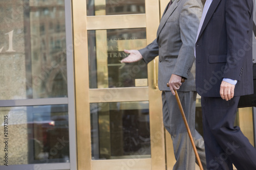 Two businessmen walking in front of a bank