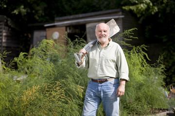 A senior man holding a spade on an allotment