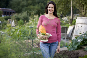A young woman holding a colander full of vegetables