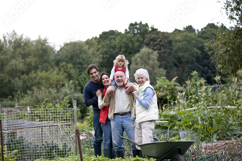 A family standing together on an allotment, laughing