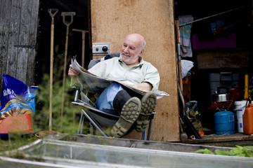 A senior man having a break on an allotment, reading a newspaper