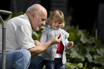 A grandfather showing a snail to his granddaughter