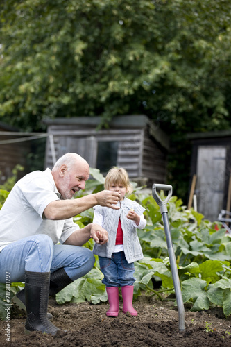 A grandfather showing a worm to his granddaughter
