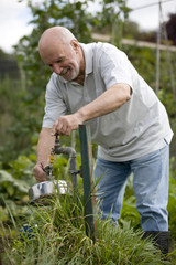 A senior man filling a kettle on an allotment