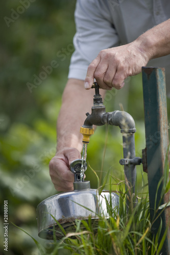 A man filling a kettle on an allotment