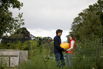 A young couple holding a pumpkin on an allotment