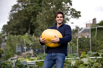 A young man holding a pumpkin on an allotment