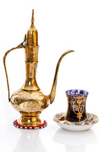 Arabic brass coffee pot with a welcoming a cup full of coffee.
