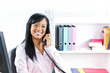 Smiling black businesswoman on phone at desk