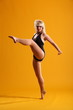 Blonde in dance pose left leg extended on yellow background