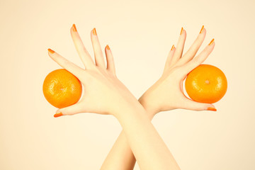 Hand with orange tangerine.