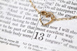 Gold necklace with heart on Bible open to 1st Corinthians 13