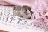 Titanium wedding rings on the Bible open to 1st Corinthians 13 poster