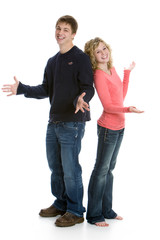 Attractive happy teenage couple standing back to back in studio