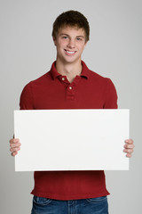 Attractive teenage boy holding a blank sign