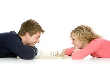 Teenage couple lying down playing chess