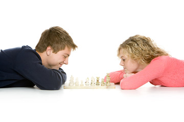 Attractive teenagers lying down playing chess