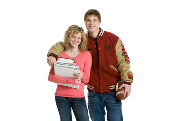 Attractive teenage couple holding books and football