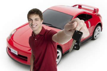 Attractive teenage boy holding car keys with car in the backgrou