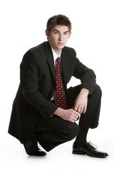 Attractive teenage boy kneeling in a suit isolated on white back