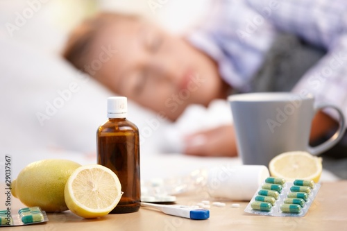Leinwanddruck Bild Vitamins medicines for flu woman in background