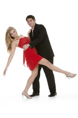Attractive teenage couple dancing and posing on isolated white b