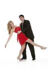 Attractive teenage couple dancing and smiling on isolated white