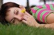 woman with dandelion lying on green grass in spring park