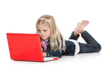Cute little girl lying down with laptop