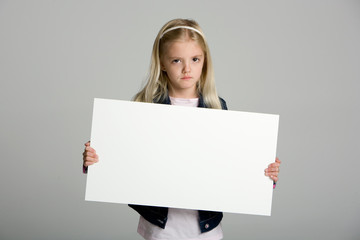 Angry little girl holding a blank sign