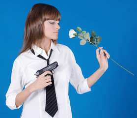 Beautiful young girl with pistol and flower in a hands