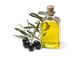 Rama de olivo con olivas negras y su aceite embotellado.