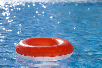 floating  ring on blue water swimpool with waves reflecting in t