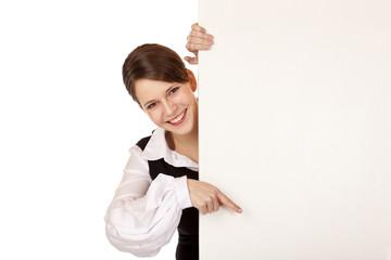 Junge lachende Frau zeigt mit Finger auf leeres Werbeschild