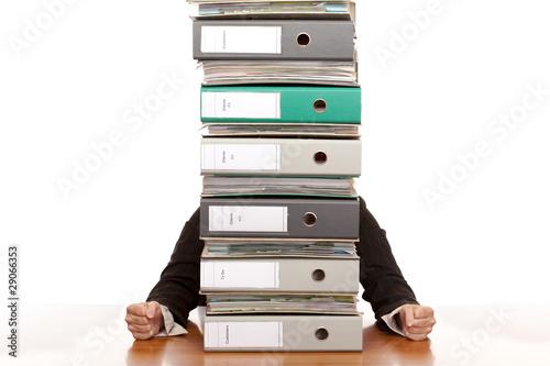 Geschäftsfrau sitzt hinter hohen Ordnerstapel und ist frustriert