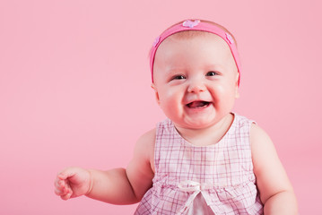 The small beautiful smiling girl on a pink background..