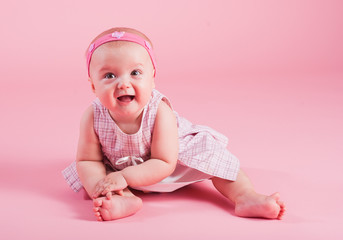 Portrait of the small joyful girl on a pink background