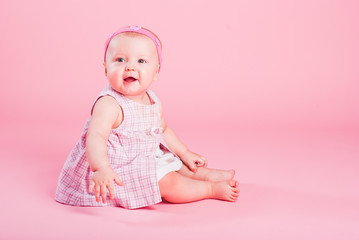 Portrait of the small beautiful joyful girl on a pink background