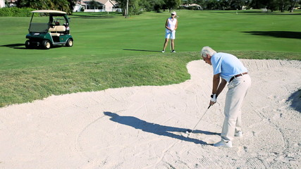 Retired Couple Keeping Active Playing Golf
