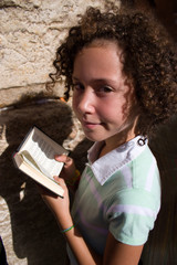 Girl with prayer book near Western Wall (Jerusalem)