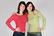 two young brunette girls in red and green shirts embracing